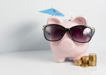 Piggy bank with sunglasses and coins on the white background