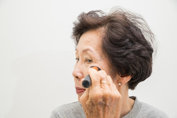 old woman applying make up