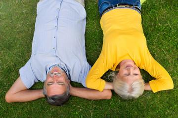 Senior couple lying on grass
