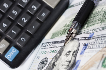 Financial statements. Calculator, dollars and pen. Close-up.