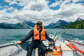 Man steering boat on Lake McDonald, Glacier National Park, Montana