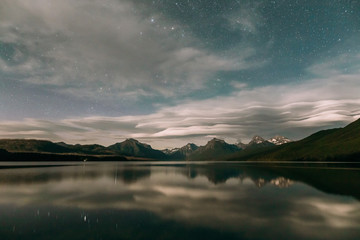 Reflection of mountain range and starry sky in Lake Mcdonald, Glacier National Park, Montana