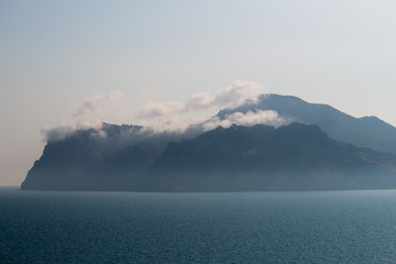 Sea covered with haze. Mountain and fog at night