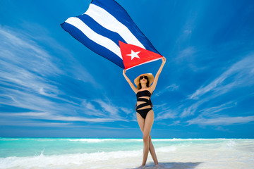 Beautiful young girl in black swimsuit is standing on the beach on the background of azure caribbean sea and holding a flag of Cuba in her arms.