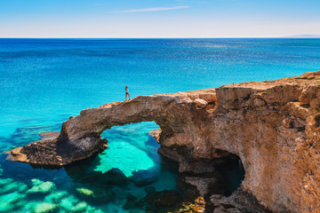 Fotobehang Cyprus Woman on the beautiful natural rock arch near of Ayia Napa, Cavo Greco and Protaras on Cyprus island, Mediterranean Sea. Legendary bridge lovers. Amazing blue green sea and sunny day.