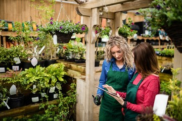 Two female florists using digital tablet