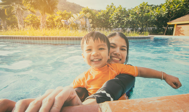Mother and son having fun in a swimming pool, vintage color toning