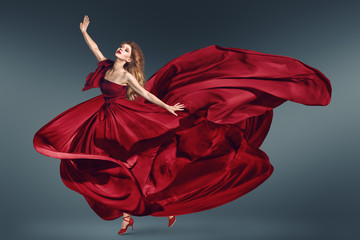 Fashion woman dancing in fluttering red dress
