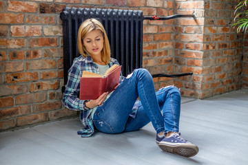 Blond female sitting on the floor and reading a book.