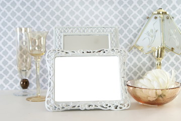 White Metal Blank Photo Frame Staged with Antique Glassware and Lamp