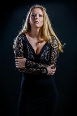 blonde girl on a black background in a dark guipure dress
