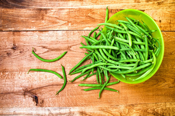 Fresh green beans in bowl on wooden table
