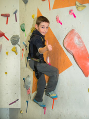 The boy climbed up on the wall and shows a hand sign ok