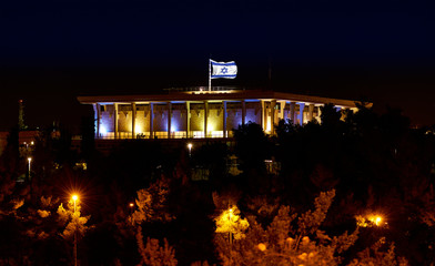 Knesset the Parliament of Israel with flying waving flag of Israel at night