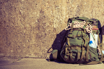 Hiking backpack camping equipment outdoor on grunge wall