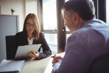Businesswoman talking with colleague while sitting in office