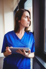 Nurse holding digital tablet and looking at window