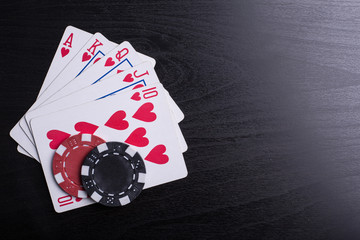 Casino poker chips and playing card with black background