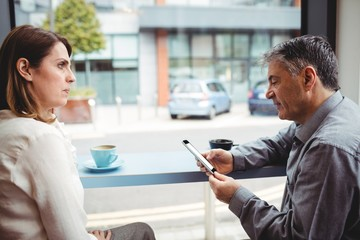 Man using mobile phone while talking with woman