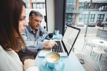 Man and woman discussing over laptop