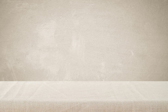 Empty table with linen tablecloth over cement wall background