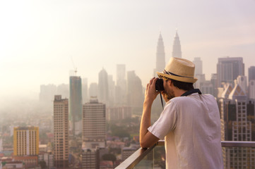Tourist taking pictures of skyscrapers at sunrise