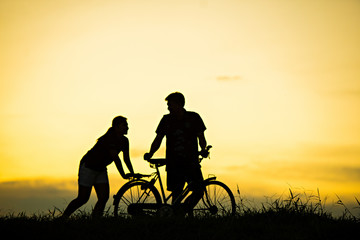 sillhouette of man and woman walking park with vintage bicycle at sunset time.
