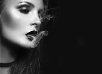 Beautiful sexy brunette girl with bright makeup, red lips, smoke from mouth. beauty face. Black and white