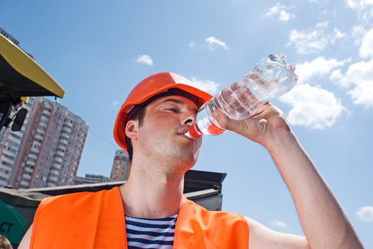 Engineer with safety vest drinking water