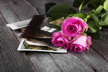 Old photos pink roses and chocolate on a dark wooden background