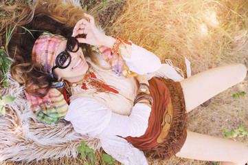 Boho style happy smiling girl portrait lying on a hay and fur
