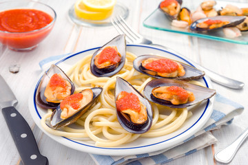 spaghetti and mussels with tomato sauce in white china