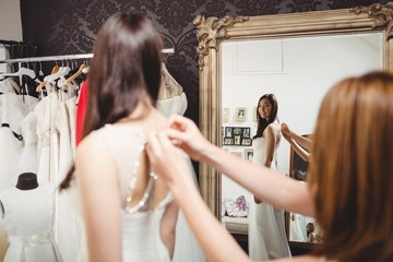 Woman trying on wedding dress with