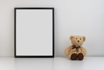 Mock up photo frame on table with a teddy bear as decoration
