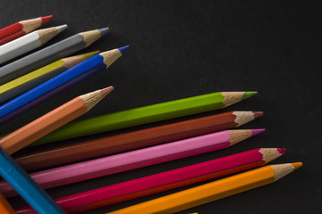 Colorful pencils on the black background close up photo with the shallow depth of field