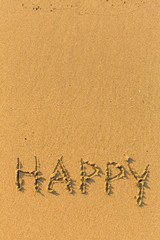 Happy - drawn on a sandy beach in the line of sea surf.