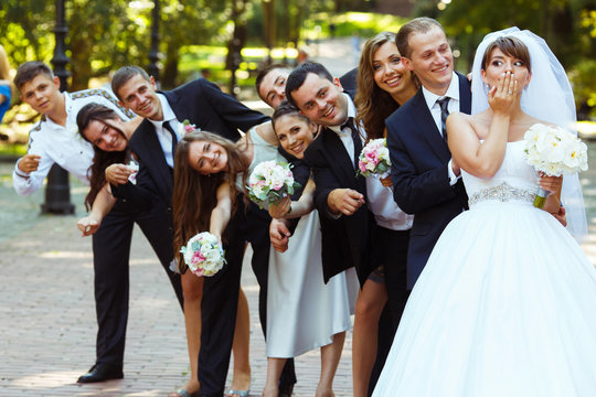 Bride closes her mouth with a palm while groom and friends look