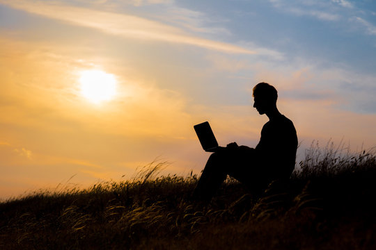 silhouette of happy business man with laptop working on the field