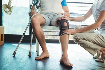 Female physiotherapist examining his patient's knee