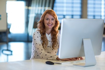 Portrait of smiling woman using computer