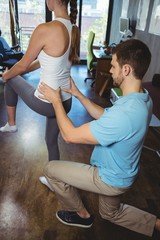 Physiotherapist correcting position of female patient