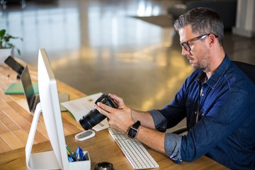 Focused man holding camera in office