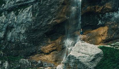 Traveler standing near the waterfall