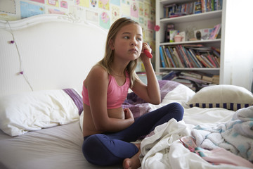 Young Girl Sitting On Bed And Brushing Hair In Bedroom