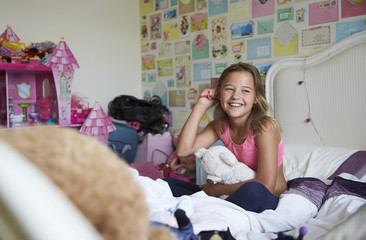 Smiling girl sitting on bed and brushing hair