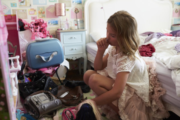 Young Girl Playing In Untidy Bedroom