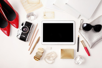 Workplace with tablet, photo camera, pen, high heels, lipstick and sunglasses. Flat lay composition. Top view