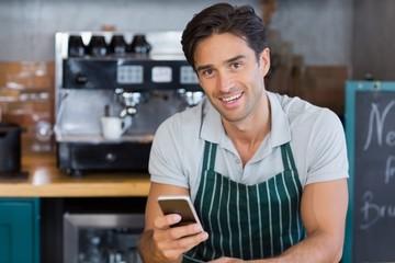 Portrait of smiling waitress using mobile phone