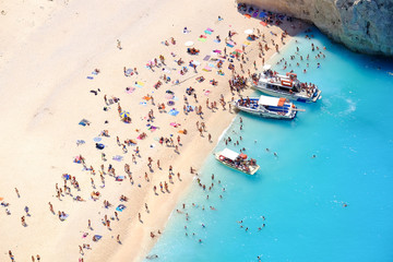 Tourists on the sand beach of Navagio Zakynthos Greece.
