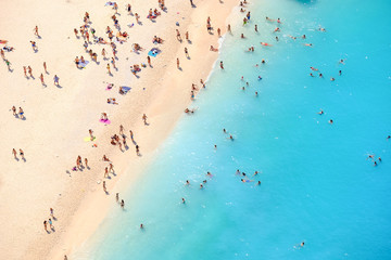 Tourists on the sand beach of Navagio Zakynthos Greece. People b